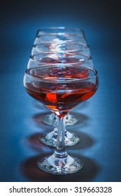Row of aligned stemmed glasses filled with red wine over blue background. Shallow depth of field.