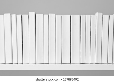 A row of all white books sit on a white shelf in front of an off white background.