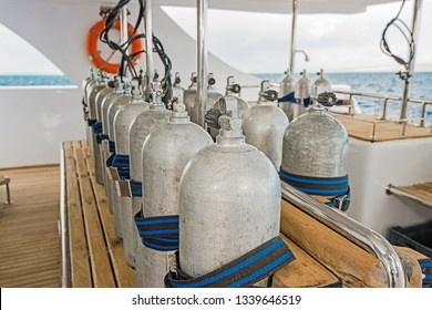 Row of aluminium scuba diving cylinders on dive deck of a luxury liveaboard motor yacht boat