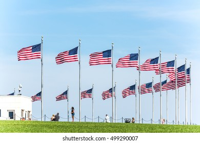 Row of American Flags by the monument at the national mall with people