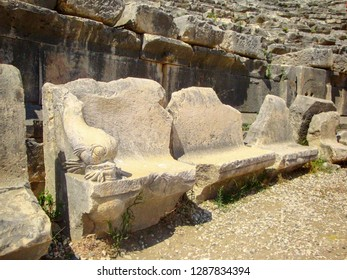 Row of ancient armchairs in a ruined amphitheater. Chairs decorated with elements resembling fish made of stone. Elements of ruins of an ancient amphitheater.