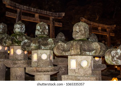 A row of ancient stone lanterns glows on a dark night in front of sacred torii gates at the entrance to a Buddhist cemetery during the obon ('return of dead spirits') festival in Japan.