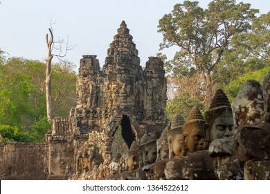 Row of angel heads on side or road leading to the South Gate entrance at the stone ruins of  Angkor Tom, Siem Reap, Cambodia.