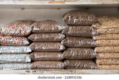 Row of animal feed pack or cereal and grain bags for pets on shelf in shop