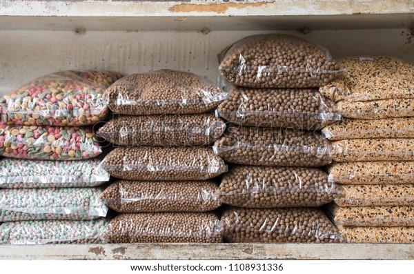 Zeile der Futterpackung oder Getreide- und Körnerbeutel für Haustiere auf dem Regal im Laden