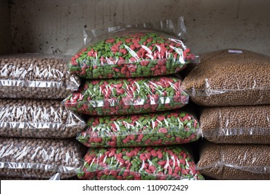 Row of animal feed package or cereal and grain bags for pets on shelf in shop