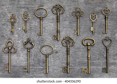 row of antique golden keys on a grunge wooden background