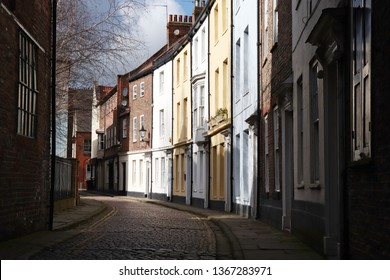 Row of apartments along a curving paved road lit by sunlight in Hull, England