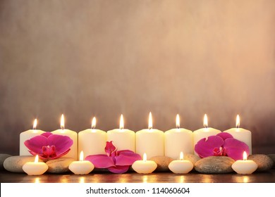 Row of aromatic candles and orchid petals.