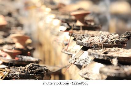 Row of ash filled censers, remnants of incense sticks, in the Dakshin Kali hindu temple, Pharping, Kathmandu, Nepal.