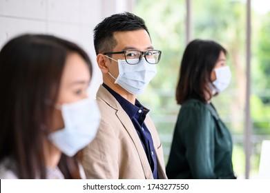 Eine Reihe asiatischer Menschen tragen Schutzmasken für Sicherheit und halten soziale Distanziertheit für einen neuen normalen Lebensstil für die Arbeit im Büro. Ein Mann, der sich die Kamera anschaut. Mensch