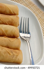 A row of Asian spring rolls and a stainless steel for on a white plate