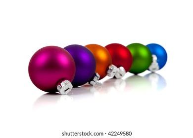 a row of assorted Christmas ornaments/baubles including pink, purple, orange, red, green and blue on a white background