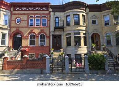 A row of attached brick apartment buildings with stoops on Lincoln Place in the Crown Heights neighborhood of Brooklyn, NY