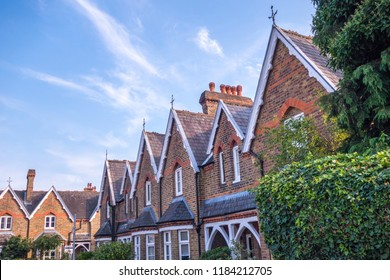 A row of attractive British brick houses against a blue sky