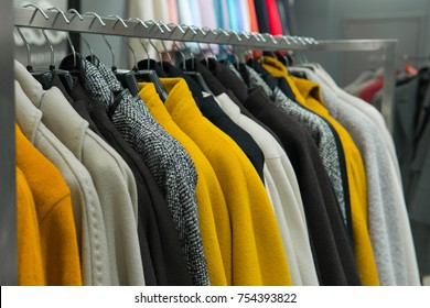 Row of autumn coats hanging on rack, shopping. Cloth shop, clothing store, female collection in fashion boutique