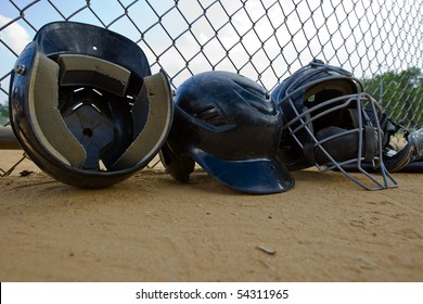 A row of batting helmets in a dugout