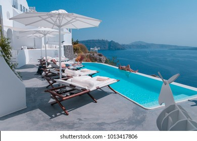 row of of beach chairs at a luxury resort swimming pool Canaves oia Santorini Greece September 2017