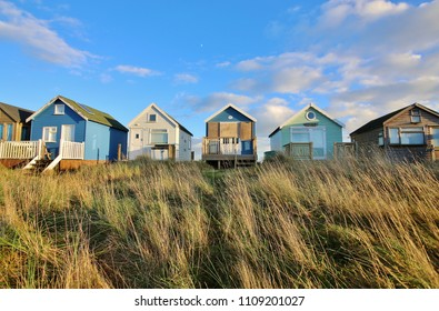 A row of beach huts facing the sun, Hengistbury Head, Bournemouth, UK