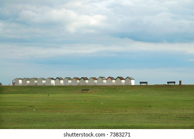 row of beach huts with grass in foreground
