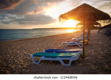 Row of beach straw umbrellas and deck chairs at sunset light