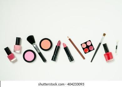 A row of beauty cometics that includes nail lacquer, lipstick, lip color, cheek blush, and brushes.