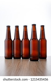 A row of beer bottles on white background. Five objects