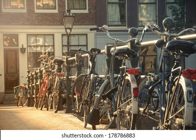 Row of bicycles against a bridge guardrail in Amsterdam, Netherlands, at sunset