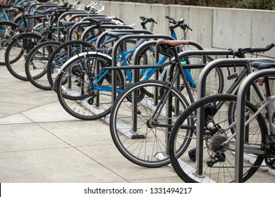 Row of bicycles locked to a bike rack, in a transportation background with space for text on the left