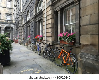 Row of bicycles on bike rack in front of a stone building.