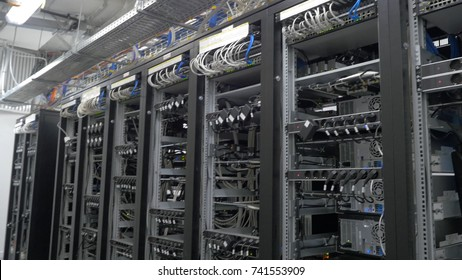 Row of bitcoin miners set up on the wired shelfs. Device for mining crypto currency. Mining cryptocurrency. Bitcoin farm. Machines for mining cryptocurrency, bitcoin. Electronic device at day.
