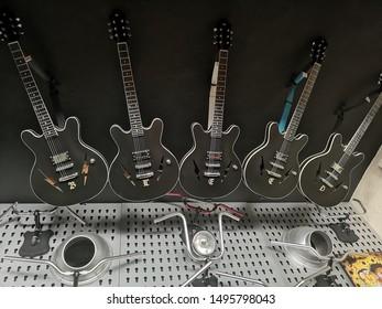 Row of black guitars put in a racks