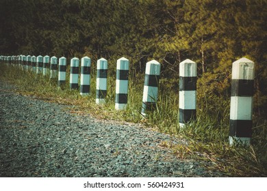 A row of black and white post roadside pillars in a rural landscape