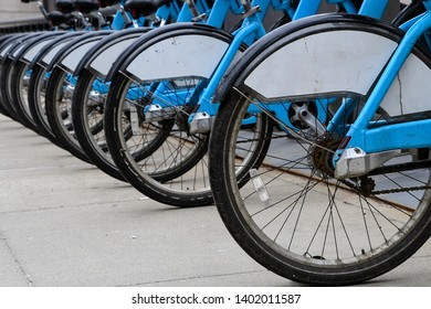 row of blue bicycles on city street