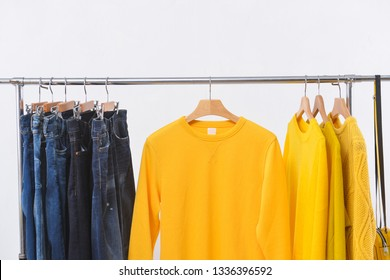 Row of blue jeans and yellow and knitted.sweater clothes on hanger-