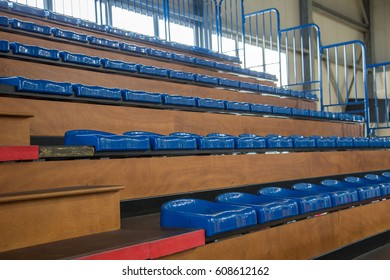 Row of blue partially numbered stadium seats. Watch a game