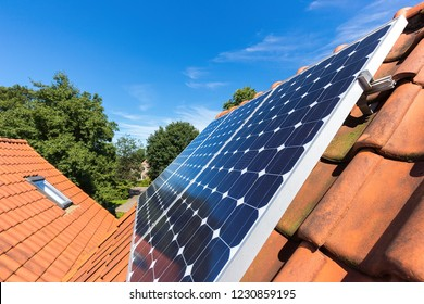 Row of blue solar collectors  on orange roof of house