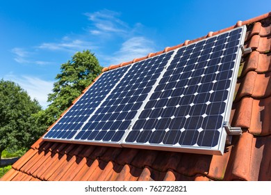 Row of blue solar panels  on roof of house