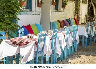 A Row Of Blue Table With Chairs At Bozcaada, Canakkale, Turkey