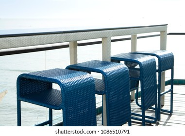 Row of blue weave bar stools with sea view in hotel or restaurant