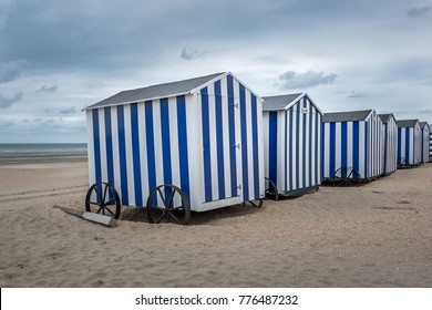 Row of blue and white beach cabins in De Panne, Belgium.