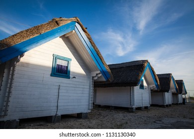 Row of blue and white painted huts in a sea resort.