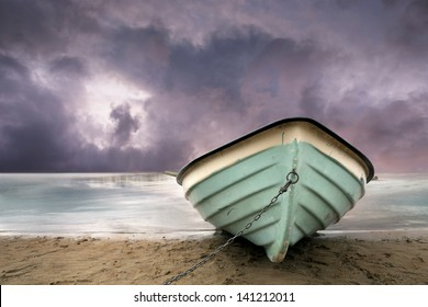 row boat on sandy beach with purple sky