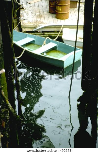 Row boat in the water between pilings