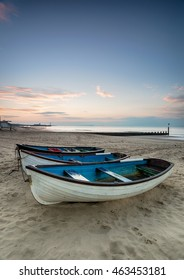 A row of boats at sunrise on Bournemouth beach in Dorset