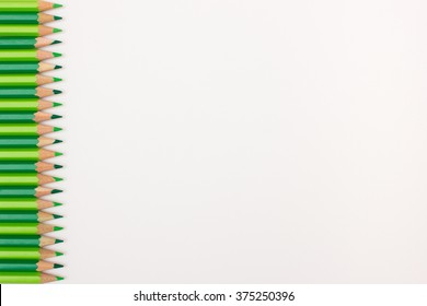 Row of bright green pencils on white background - useful background image for sign, presentation slides with copy space available