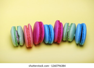 A row of bright macaroons of different color