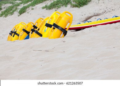 Row of bright yellow floatation rescue devices and surf-ski on beach