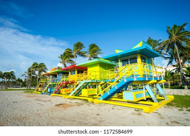 Row of brightly painted colorful lifeguard towers with coconut palm trees on Miami Beach promenade.