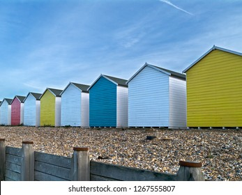 Row of brightly painted colourful wooden beach huts on Eastbourne shingle beach with blue sky above, Eastbourne, East Sussex, England, UK